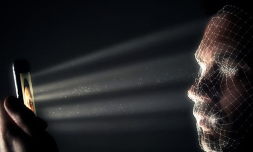 The phones light reflecting on the man's face